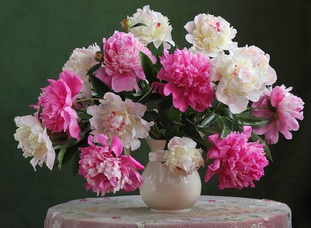 Schöner blumenstrauß von rosa und weißen pfingstrosen steht auf einem runden tisch in einem krug.