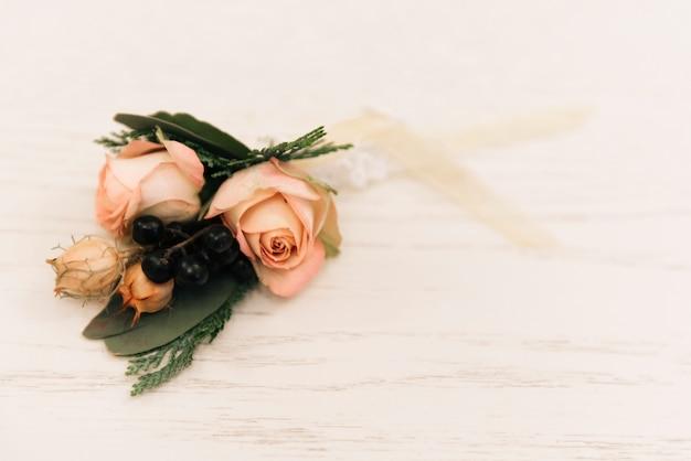 Schöner boutonniere mit einer rose im rustikalen stil liegt auf einem weißen hintergrund, kopierraum