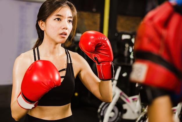 Schöner boxer der asiatischen frau, der das boxen in einer turnhalle übt.