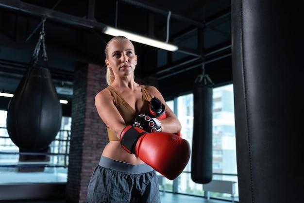 Schöner boxer. schöne boxerin, die leuchtend rote handschuhe trägt, die durch boxsäcke umgeben stehen