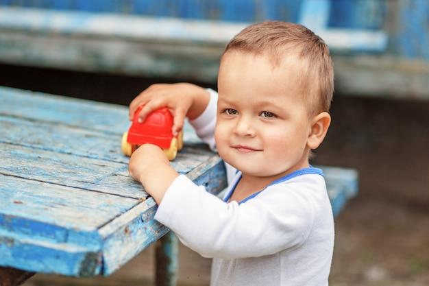 Schöner braunäugiger kleiner junge, der mit einer roten plastikspielzeugmaschine draußen spielt