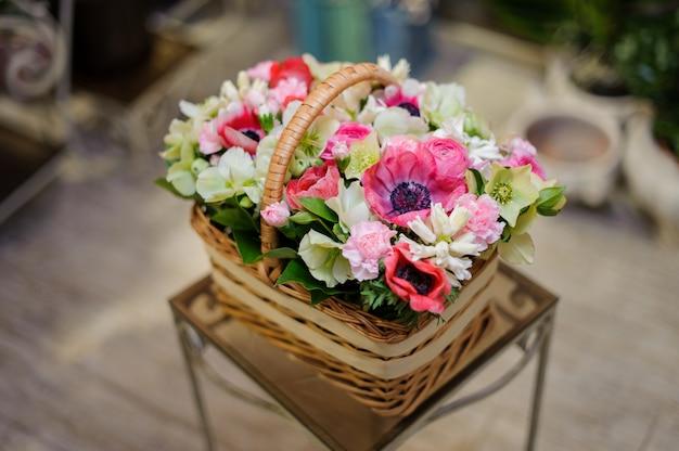 Schöner brauner weinlesekorb der rosa und weißen blumen
