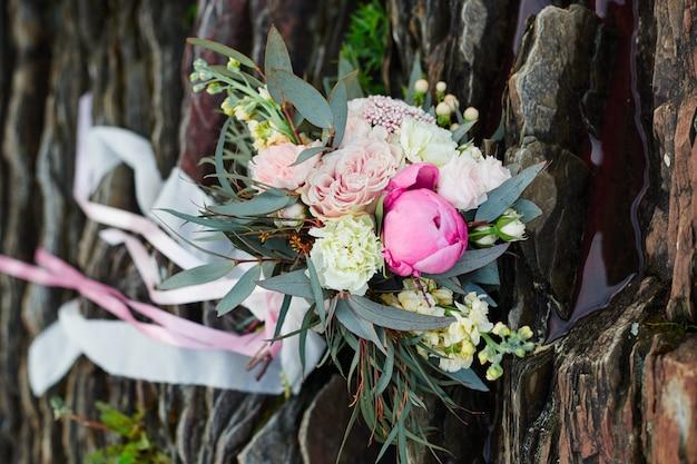 Schöner brautblumenstrauß, der auf den steinen liegt. ein strauß für die trauung des mädchens