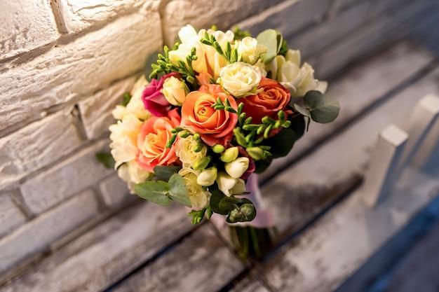 Schöner brautstrauß. rosen in der nähe der weißen mauer. weinlesehintergrund. hochzeitszubehör nahaufnahme.