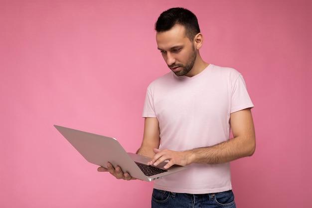 Schöner brunet-mann, der laptop-computer hält und auf der tastatur tippt und auf den netbook-monitor im t-shirt auf isoliertem rosa hintergrund schaut