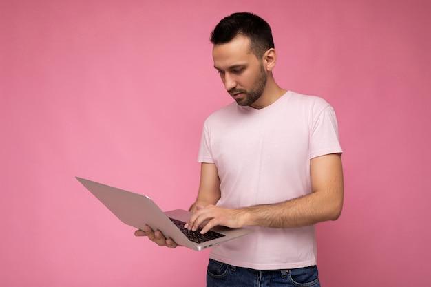 Schöner brunet-mann, der laptop-computer hält und auf der tastatur tippt