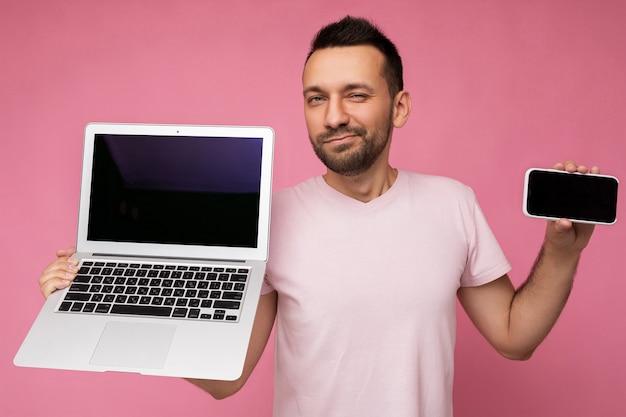 Schöner brunet-mann, der laptop-computer und mobiltelefon hält und die kamera im t-shirt auf isoliertem rosa hintergrund betrachtet.
