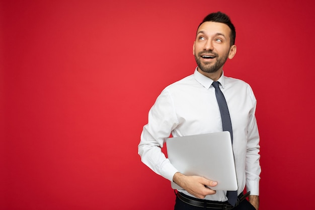 Schöner brunet-mann mit laptop-computer, der in weißem hemd und krawatte nach oben schaut
