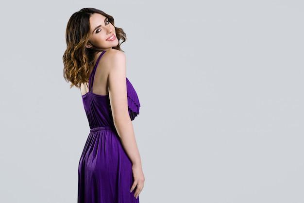 Schöner brunette im violetten kleid auf hellem hintergrund