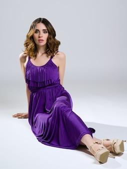 Schöner brunette im violetten kleid auf licht