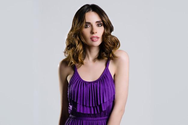 Schöner brunette im violetten kleid