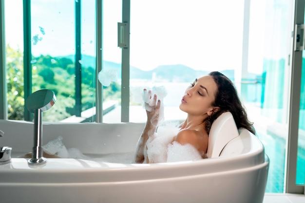 Schöner brunette sitzt in einem bad und bläst schaum mit den händen auf