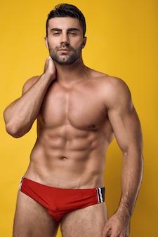 Schöner brutal gebräunter muskulöser mann, der eine rote unterwäsche trägt