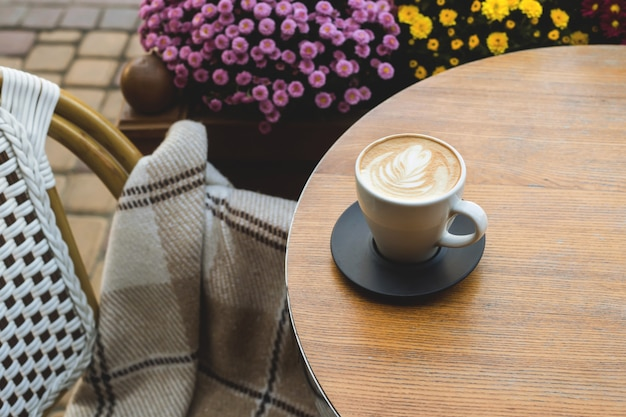 Schöner cappuccino mit kunst in einer weißen schale auf der straßentabelle eines stadtcafés.