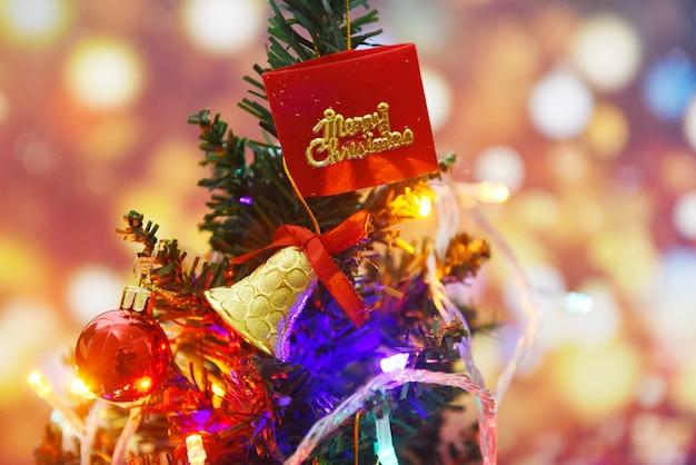 Schöner dekorationsweihnachtsbaum auf unscharfem buntem bokeh - weihnachtsbaum mit ballgeschenkboxstern und -lichtern verzierte innenraum der kiefer neujahrsfeiertags-festivalfeier zu hause