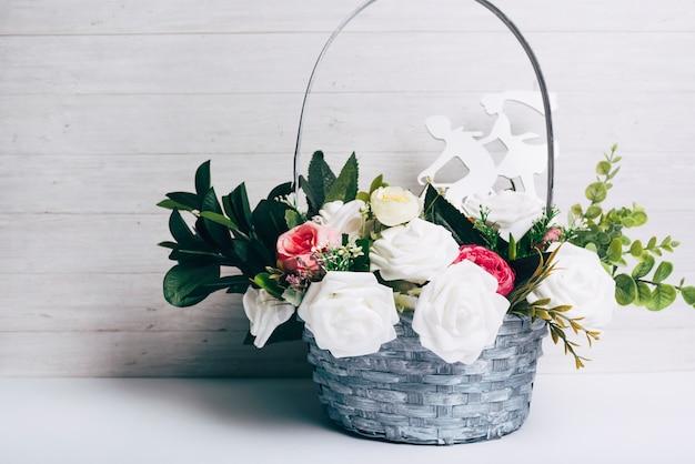 Schöner dekorativer rosenblumenstrauß mit herausgeschnittener zahl gegen hölzernen hintergrund