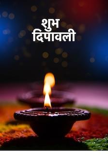 Schöner diwali-gruß mit diya- oder tonöllampe beleuchtet und über rangoli angeordnet, hergestellt aus mehrfarbigen reiskörnern, selektiver fokus