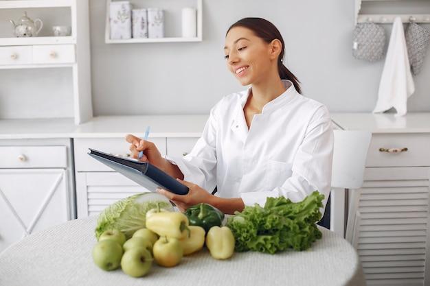 Schöner doktor in einer küche mit gemüse