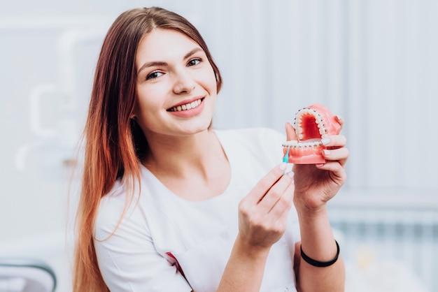 Schöner doktorkieferorthopäde zeigt ihnen, wie man für ihre zähne sich interessiert