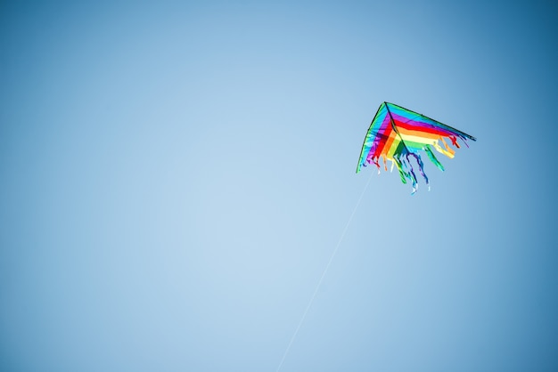 Schöner drachen in den hellen farben des regenbogens fliegt gegen einen sonnigen blauen himmel.