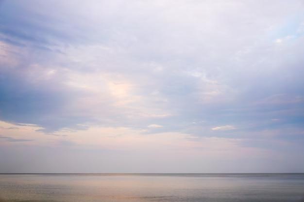 Schöner dramatischer bewölkter himmelssonnenunterganghintergrund unter meerwasser mit gelb-orangefarbenen farben