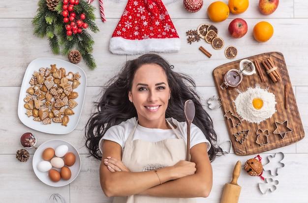 Schöner dunkelhaariger koch, der auf dem boden liegt und weit lächelt, den holzlöffel hält und von lebkuchen, eiern, mehl, weihnachtsmütze, getrockneten orangen und backformen umgeben ist.