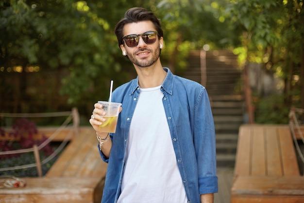 Schöner dunkelhaariger mann in der freizeitkleidung, die über grünem stadtpark am sonnigen warmen tag aufwirft, tasse limonade hält und mit weichem lächeln schaut