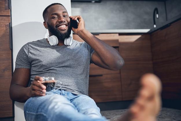 Schöner dunkelhäutiger mann, der beim telefonieren ein lächeln auf dem gesicht behält