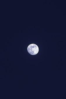 Schöner einsamer weißer mond im dunkelblauen himmel