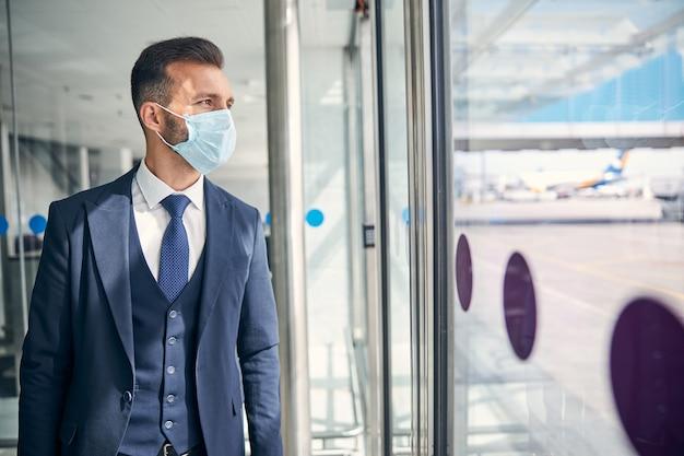 Schöner eleganter mann in einem anzug, der eine medizinische maske trägt und durch die glastür eines flughafens schaut. website-banner