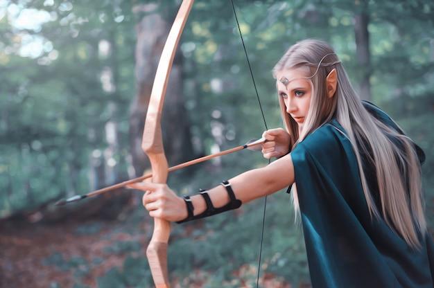 Schöner elfenfrauenbogenschütze im wald, der mit einem bogen jagt