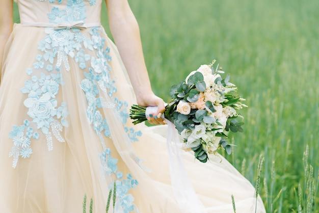 Schöner empfindlicher hochzeitsblumenstrauß in der rustikalen art mit einem weißen band in den händen