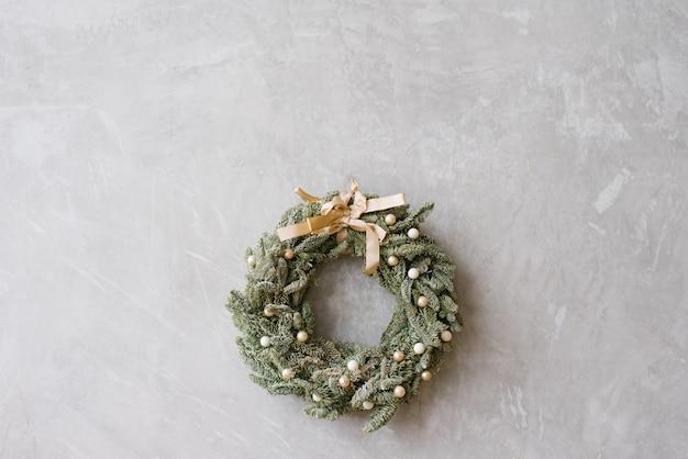 Schöner empfindlicher weihnachtskranz mit beige bogen auf grauer wand, kopienraum