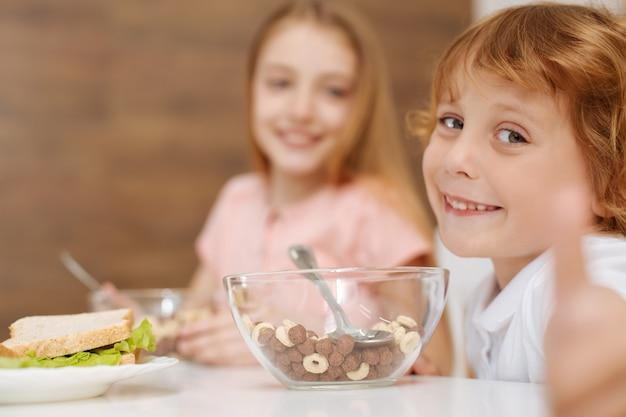 Schöner energischer, aufrichtiger junge, der am tisch sitzt und süßes müsli isst, während er zeigt, wie sehr er es genießt