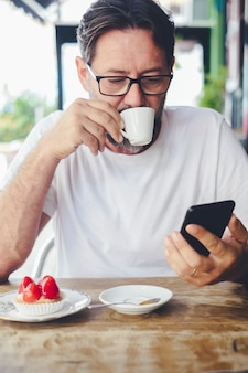 Schöner erwachsener mann, der kaffee trinkt und das handy auf e-mails oder nitifications überprüft. moderne, reife leute im café, die eine drahtlose internetverbindung genießen