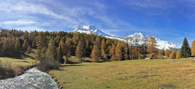Schöner europäischer alpenberg mit schneebedecktem gipfel und fluss im panoramablick