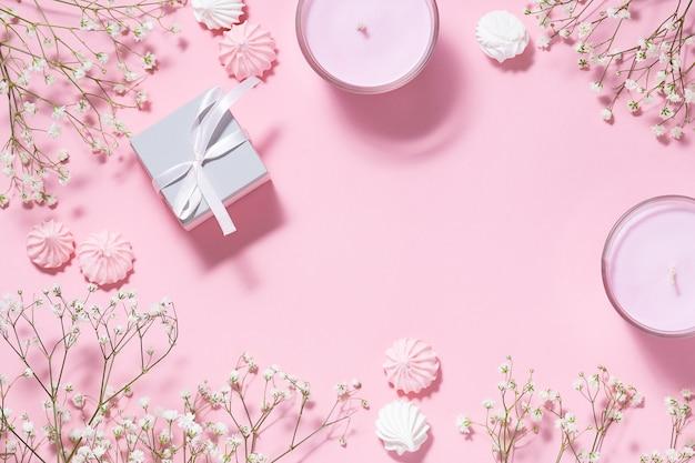 Schöner festlicher rahmen mit frühlingsblumen-merengue-keksen und aromatischen kerzen