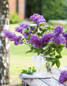 Schöner fliederstrauß in einer vase auf holztisch in der natur
