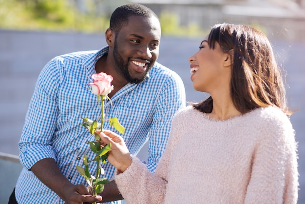 Schöner flirty attraktiver kerl, der seine freundin überrascht, indem er ihr blumen bringt, während sie ein date im park haben