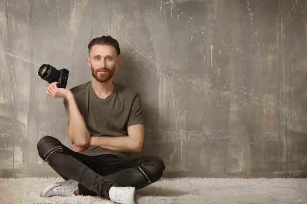 Schöner fotograf, der auf dem boden in der nähe der grunge-wand sitzt sitting