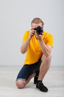 Schöner fotograf mit kamera, auf grauer oberfläche