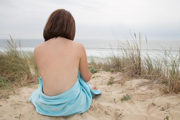 Schöner frauenakt, der von der rückseite auf strand sitzt