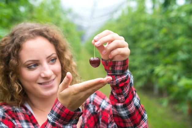 Schöner frauenbauer, der kirschfrucht im grünen obstgarten hält