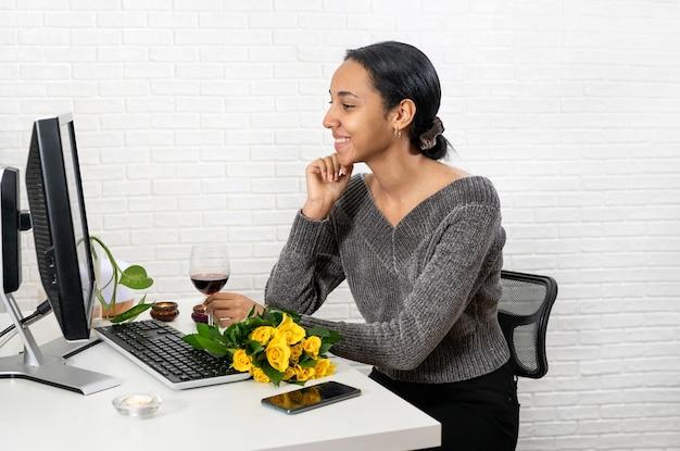 Schöner frauenbündel, der romantisches online-treffen mit jemandem am computer zu hause spricht. technologiekonzept. neue normalität. valentinstag