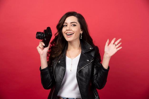 Schöner frauenfotograf, der fotokamera auf einem roten hintergrund hält. foto in hoher qualität
