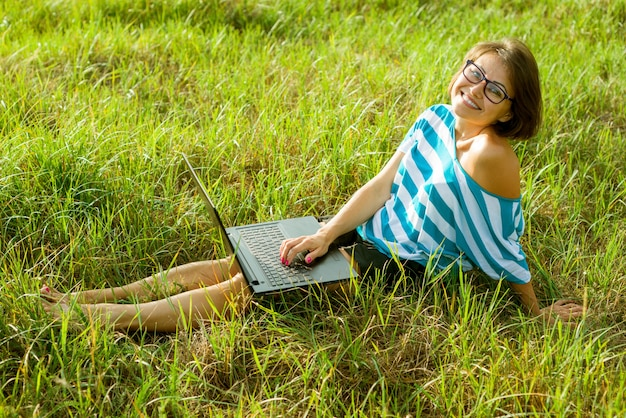 Schöner frauenfreiberufler, der draußen mit laptop arbeitet