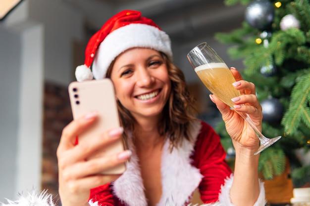 Schöner frauenhut und roter weihnachtsmann, der glücklich lächelt, champagnerglas, konzeptfeiertag feiernd, weihnachtsbaumhintergrund geschlossen. weihnachtsgrüße im internet. quarantäne zum neuen jahr.