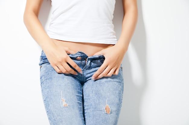 Schöner frauenkörper in denim-jeans über weiß