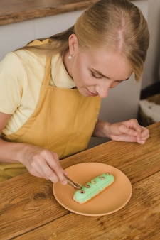 Schöner frauenkonditor verziert das eclair. süßwaren- oder kochkurskonzept