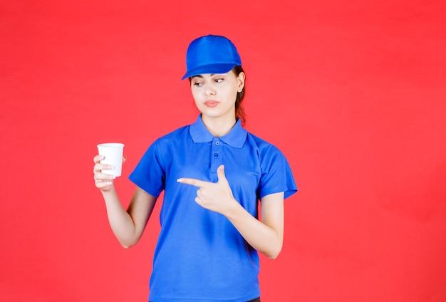 Schöner frauenkurier in der blauen ausstattung, die tasse tee auf rot hält.
